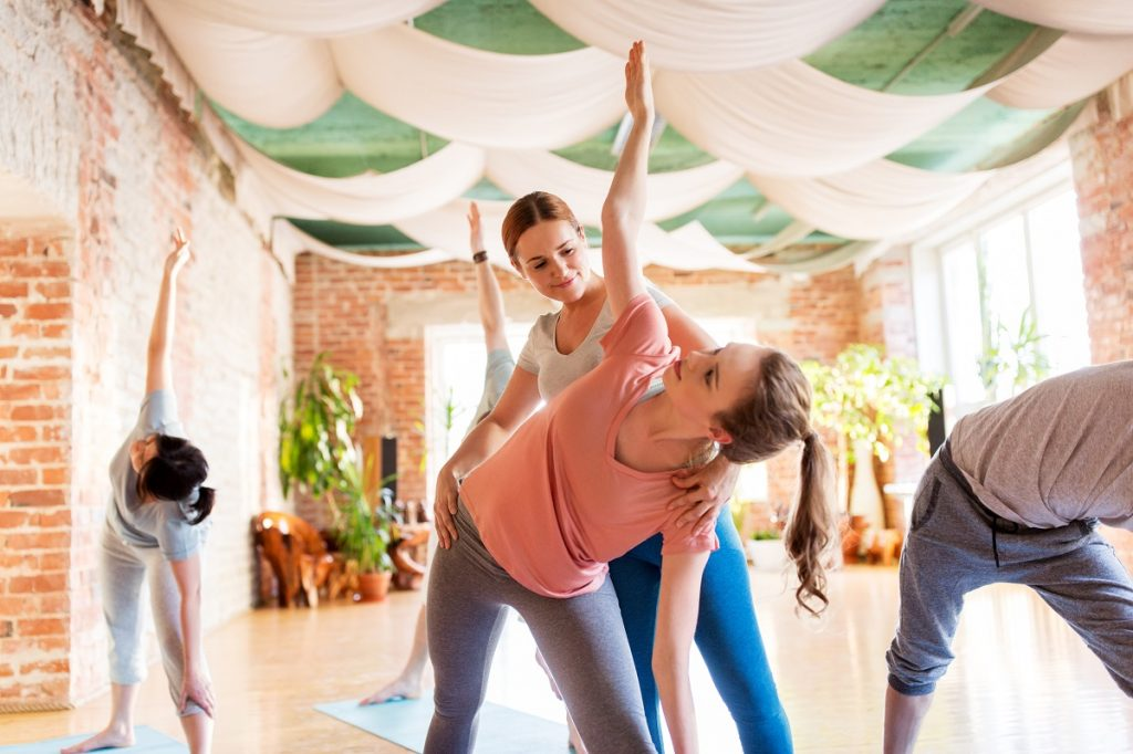 Yoga instructor assisting her student