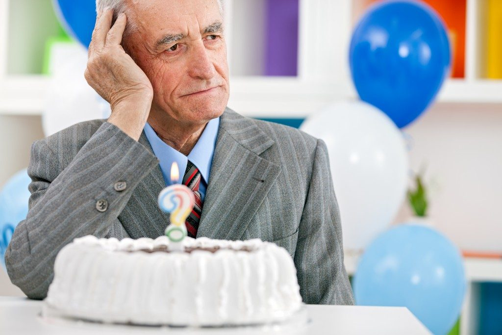 Senior man sitting front of birthday cake