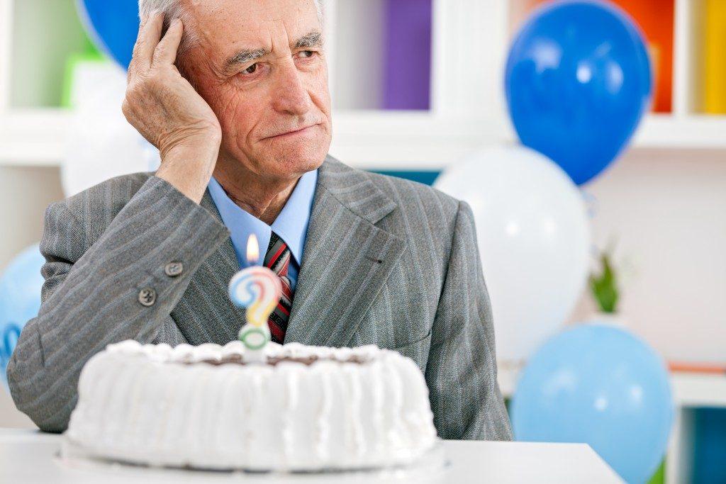 Senior man sitting front of birthday cake