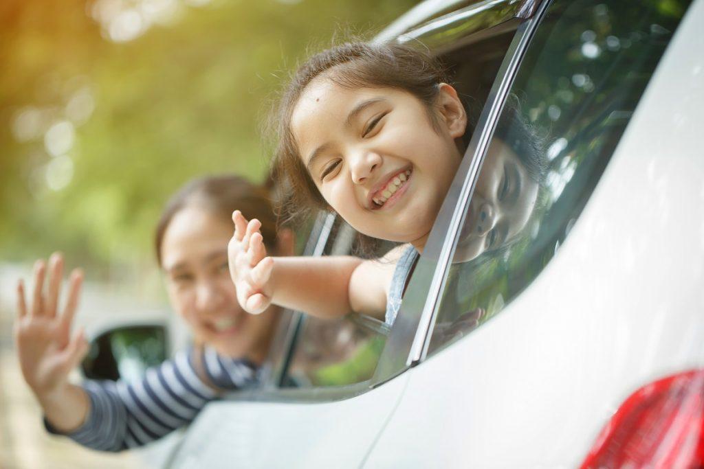Little girl and mom smiling inside their minivan