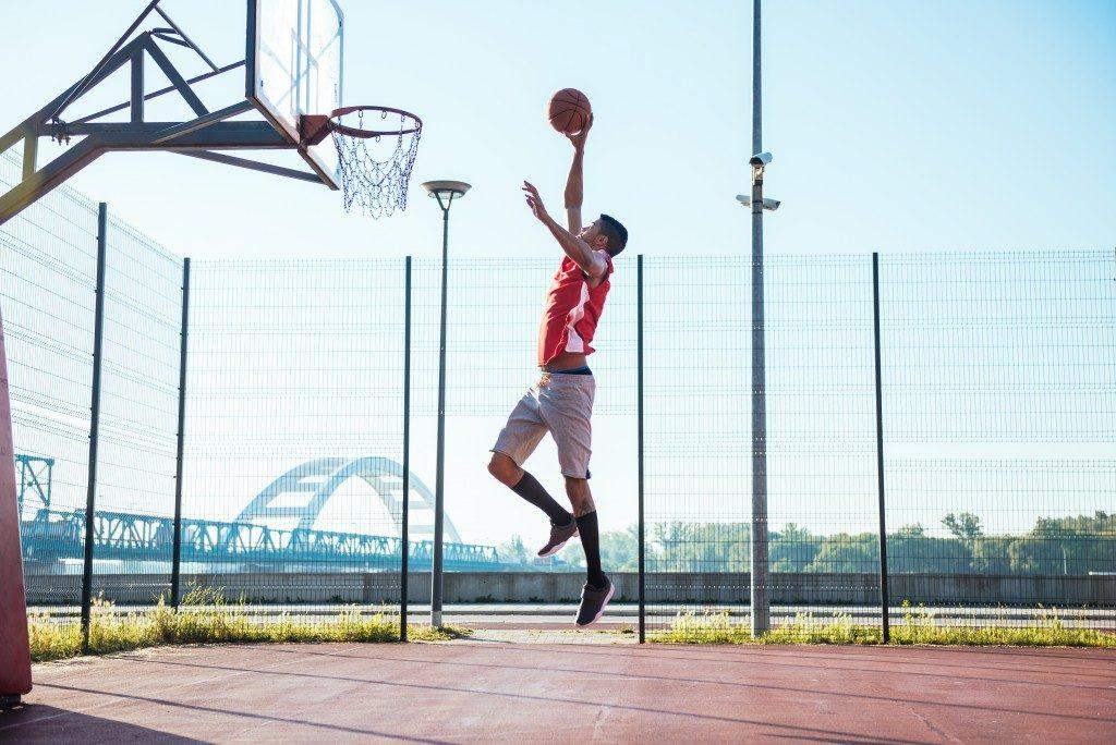 man playing basketball alone