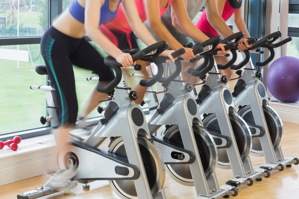 Mid section of four people working out at exercise bike class in gym