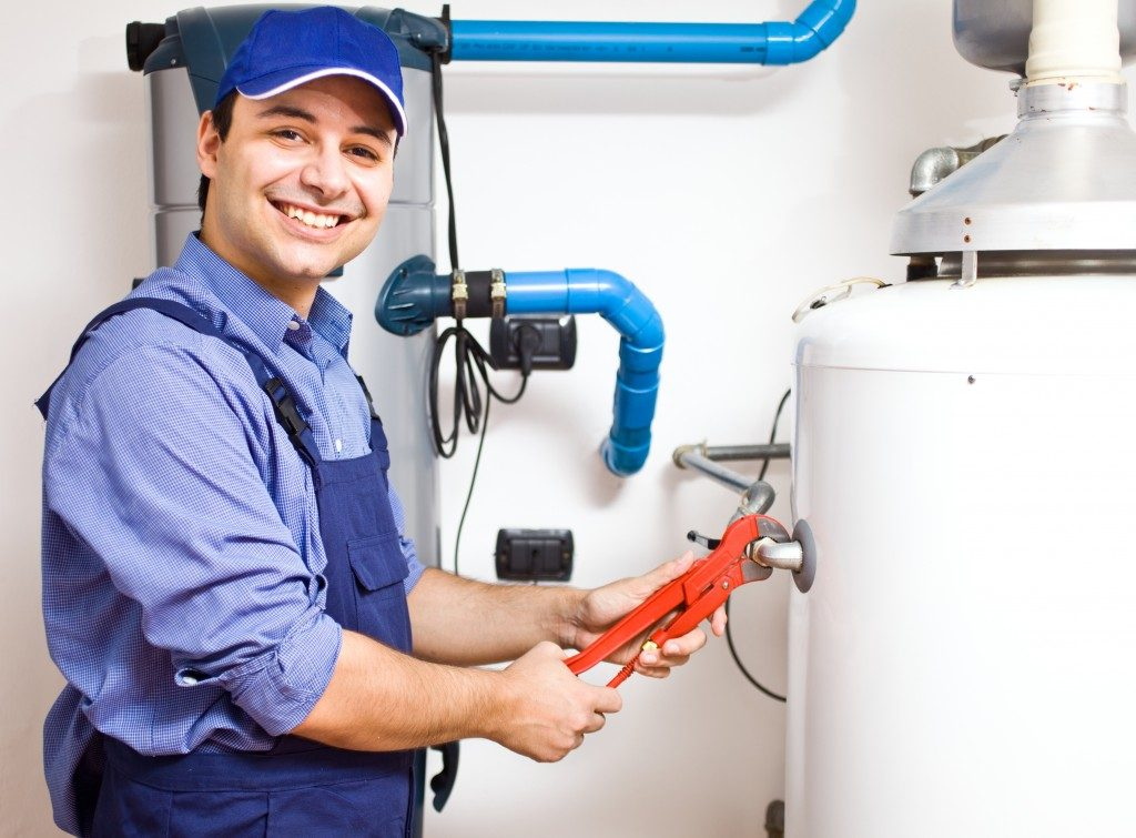 Plumber repairing the gas water heater