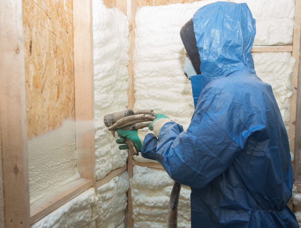 contractor wearing protective gear applying adhesive foam