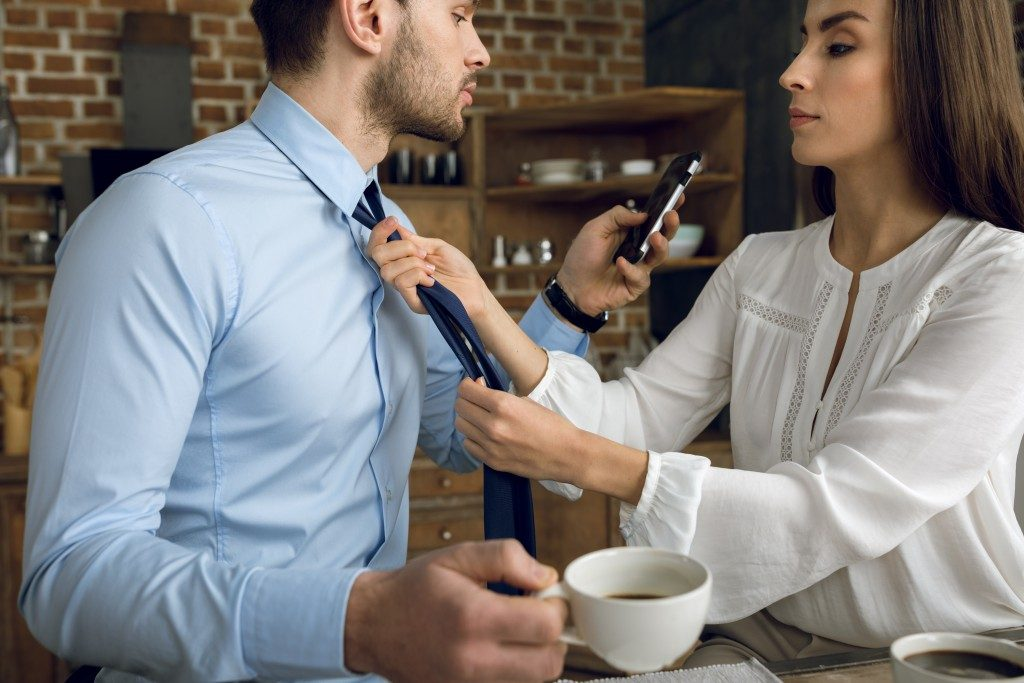 woman fixing a man's tie