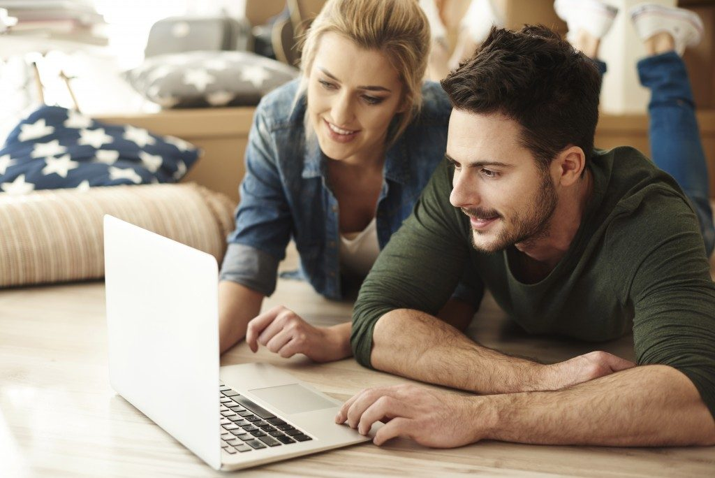 couple at home looking at laptop screen