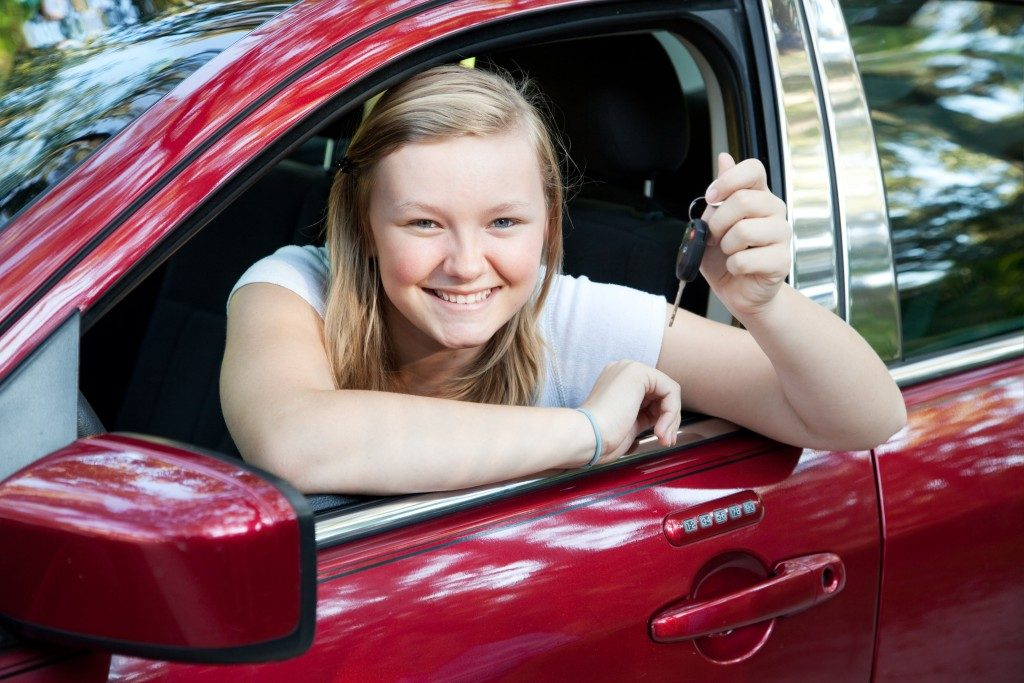 teenage girl sitting in her new car, holding the keys