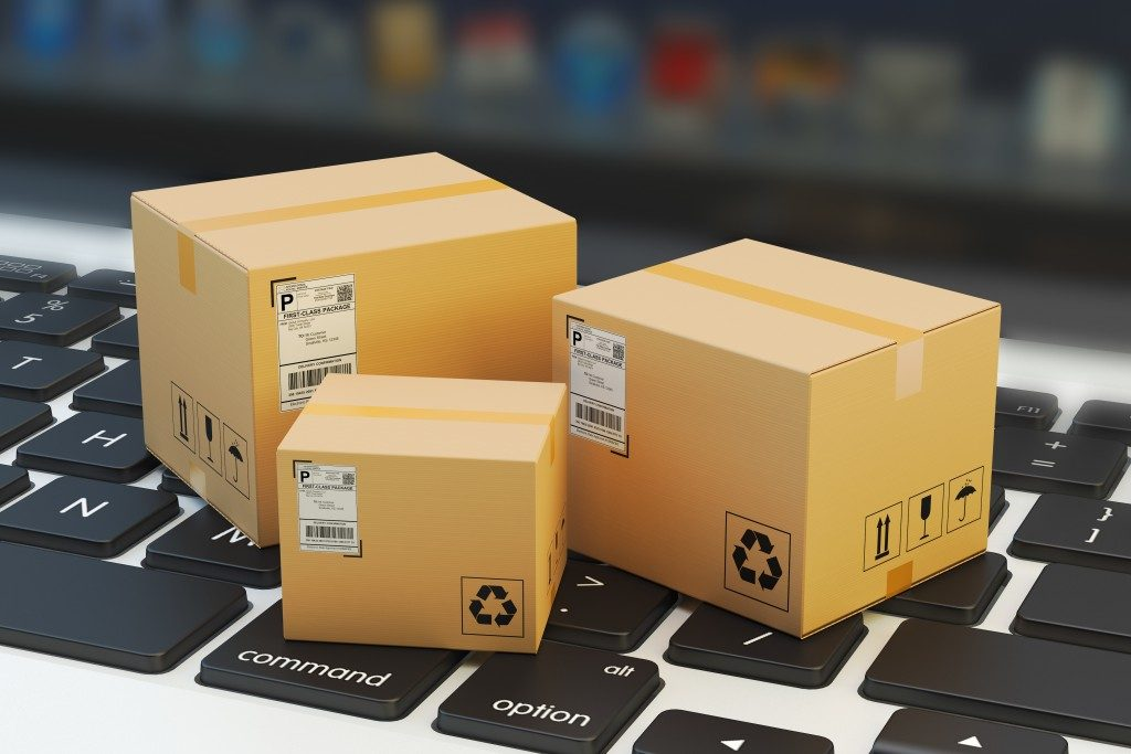 Online shopping concept with packaging boxes over laptop