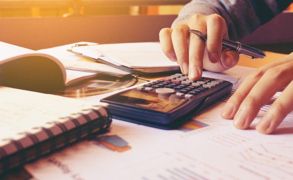 businessman calculating costs using calculator