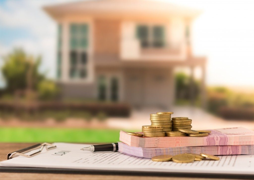 Money and loan contract in front of a home