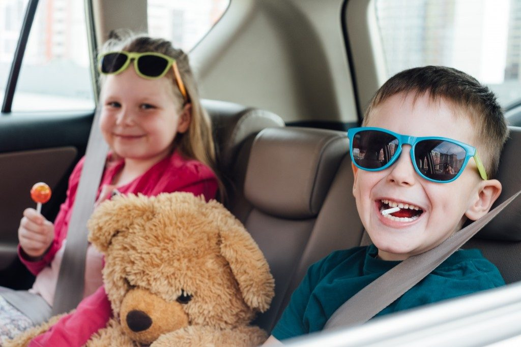kids in the car wearing colorful sunglasses and having lollipop