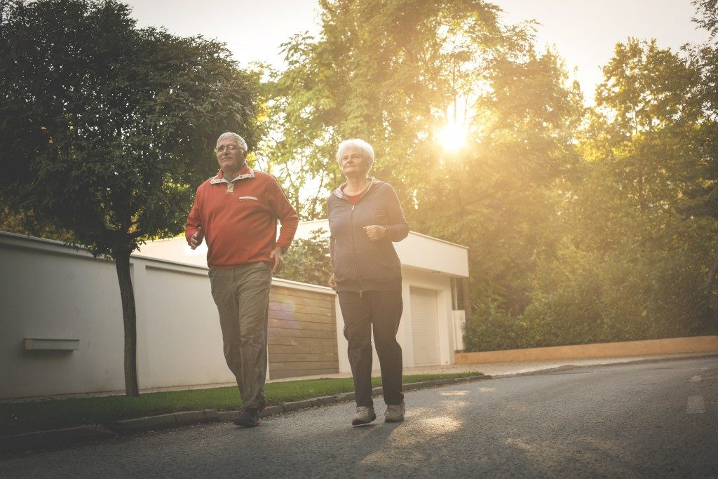 senior couple jogging in the village