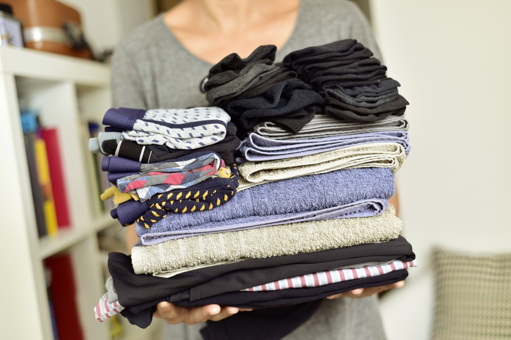carrying a pile of different folded clothes