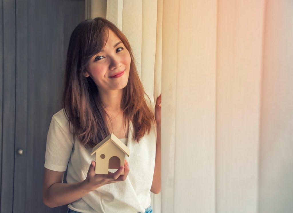 woman holding a house miniature