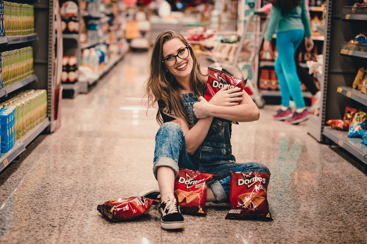 woman holding bags of chips