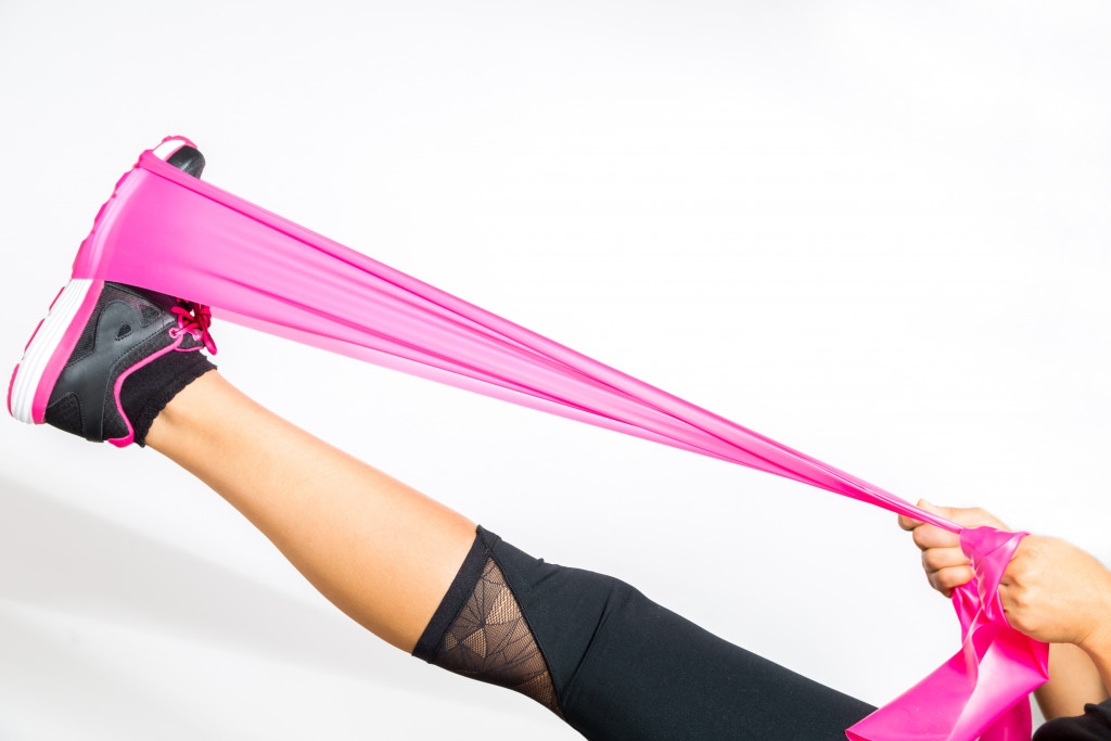 Woman exercises with resistance bands around her feet.